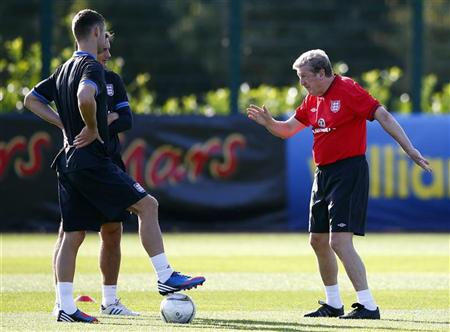 England's manager Roy Hodgson talks with Frank Lampard and Gary Cahill during a soccer training session in London Colney
