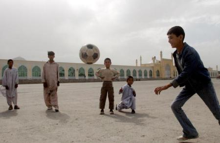Afghan youths play football in front of